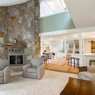 クリーブランドの中くらいのビーチスタイルのおしゃれなLDK (緑の壁、カーペット敷き、コーナー設置型暖炉、石材の暖炉まわり、壁掛け型テレビ、白い床) の写真