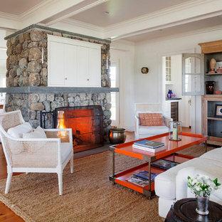 プロビデンスの大きいビーチスタイルのおしゃれなLDK (白い壁、両方向型暖炉、石材の暖炉まわり、内蔵型テレビ、淡色無垢フローリング) の写真