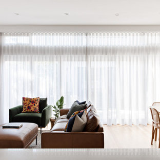 Photo of a mid-sized contemporary open concept living room in Sydney with white walls, light hardwood floors, a wall-mounted tv and beige floor.