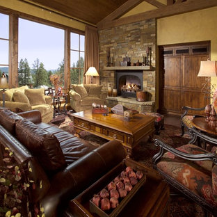 Huge tuscan formal and open concept medium tone wood floor living room photo in Phoenix with a standard fireplace, a stone fireplace, yellow walls and a concealed tv