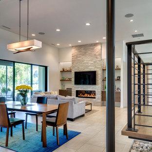 シアトルの中サイズのモダンスタイルのおしゃれなLDK (白い壁、磁器タイルの床、横長型暖炉、石材の暖炉まわり、壁掛け型テレビ、白い床) の写真