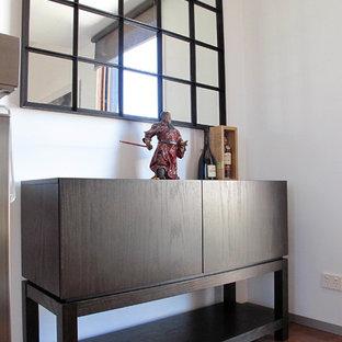 Imagen de biblioteca en casa abierta, contemporánea, pequeña, con paredes blancas, suelo de madera clara, chimenea tradicional, marco de chimenea de metal, televisor retractable y suelo naranja