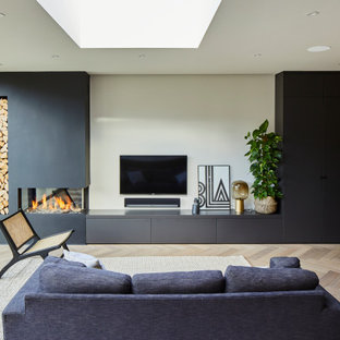 Inspiration for a contemporary open plan living room in Surrey with beige walls, light hardwood flooring, beige floors, a corner fireplace, a plastered fireplace surround and a wall mounted tv.