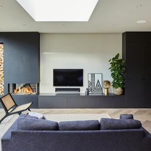 Immagine di un soggiorno contemporaneo aperto con pareti beige, parquet chiaro, pavimento beige, camino ad angolo, cornice del camino in intonaco e TV a parete