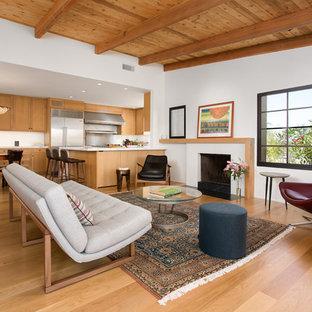 ロサンゼルスの中くらいのミッドセンチュリースタイルのおしゃれなLDK (白い壁、淡色無垢フローリング、標準型暖炉、漆喰の暖炉まわり、テレビなし、黄色い床) の写真