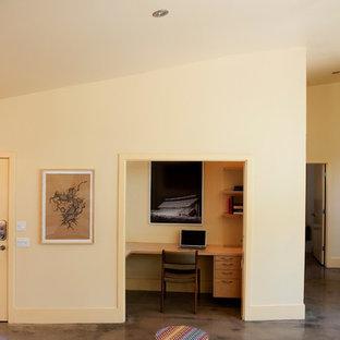 Imagen de salón para visitas abierto, contemporáneo, de tamaño medio, con suelo de cemento, pared multimedia y paredes amarillas