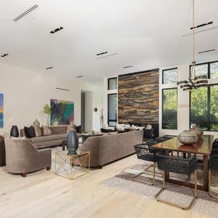 ロサンゼルスの巨大なコンテンポラリースタイルのおしゃれなLDK (フォーマル、白い壁、淡色無垢フローリング、横長型暖炉、石材の暖炉まわり、テレビなし、ベージュの床) の写真