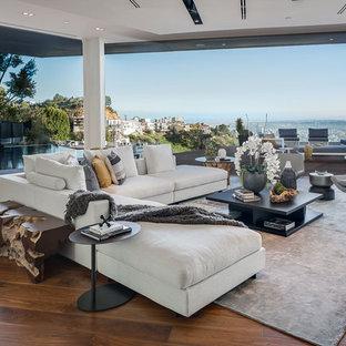 ロサンゼルスの巨大なモダンスタイルのおしゃれなLDK (フォーマル、白い壁、無垢フローリング、横長型暖炉、石材の暖炉まわり、テレビなし) の写真