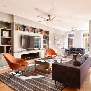 Trendy open concept medium tone wood floor and brown floor living room photo in Philadelphia with gray walls, a ribbon fireplace, a plaster fireplace and a wall-mounted tv