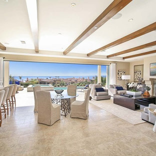 Large tuscan open concept limestone floor and beige floor living room photo in Orange County with beige walls, a standard fireplace, a stone fireplace and a wall-mounted tv