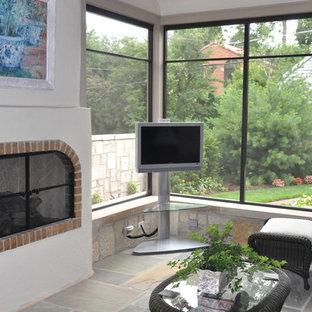 シカゴの中サイズのトラディショナルスタイルのおしゃれな独立型リビング (白い壁、標準型暖炉、据え置き型テレビ、スレートの床、レンガの暖炉まわり、マルチカラーの床) の写真