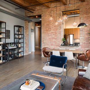 Ispirazione per un soggiorno industriale di medie dimensioni e aperto con pareti grigie, parquet scuro e camino classico