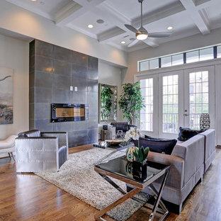 Idee per un grande soggiorno chic stile loft con angolo bar, pareti verdi, parquet scuro, camino classico, cornice del camino in metallo e TV a parete