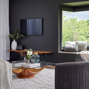 This is an example of a large contemporary open concept living room in Brisbane with black walls, medium hardwood floors, a wall-mounted tv, brown floor and planked wall panelling.