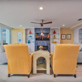 マイアミの中サイズのビーチスタイルのおしゃれなリビング (黄色い壁、磁器タイルの床、横長型暖炉、石材の暖炉まわり、壁掛け型テレビ) の写真