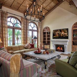 マイアミの大きい地中海スタイルのおしゃれなリビング (ベージュの壁、標準型暖炉、壁掛け型テレビ) の写真