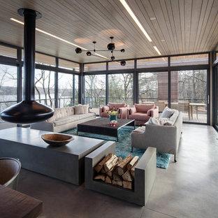 ニューヨークのコンテンポラリースタイルのおしゃれなLDK (吊り下げ式暖炉、コンクリートの床、テレビなし) の写真