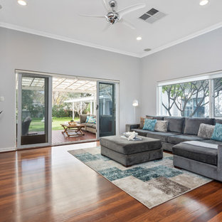 Large contemporary living room in Perth with grey walls, brown floor, medium hardwood floors and a freestanding tv.