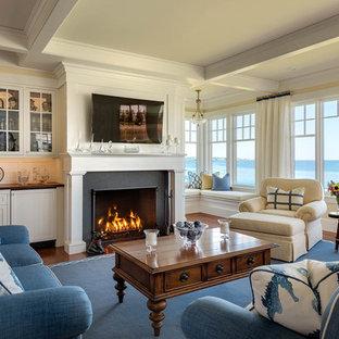 ポートランド(メイン)の中サイズのビーチスタイルのおしゃれなLDK (黄色い壁、無垢フローリング、標準型暖炉、石材の暖炉まわり、壁掛け型テレビ) の写真