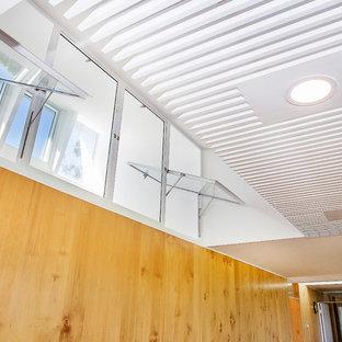 Immagine di un grande soggiorno minimal aperto con pavimento in pietra calcarea, stufa a legna, cornice del camino piastrellata, TV nascosta, pareti bianche e pavimento grigio