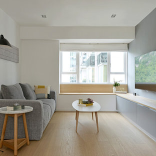 Свежая идея для дизайна: гостиная комната в скандинавском стиле с серыми стенами, светлым паркетным полом и телевизором на стене - отличное фото интерьера