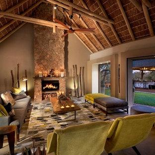Immagine di un soggiorno tropicale di medie dimensioni con sala formale, pareti grigie, camino classico, cornice del camino in pietra e pavimento grigio
