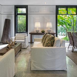 マイアミの広いトロピカルスタイルのおしゃれなリビング (白い壁、コンクリートの床、標準型暖炉、石材の暖炉まわり、テレビなし、グレーの床) の写真