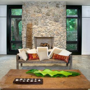 マイアミの大きいトロピカルスタイルのおしゃれなリビング (ベージュの壁、コンクリートの床、標準型暖炉、石材の暖炉まわり、テレビなし、グレーの床) の写真