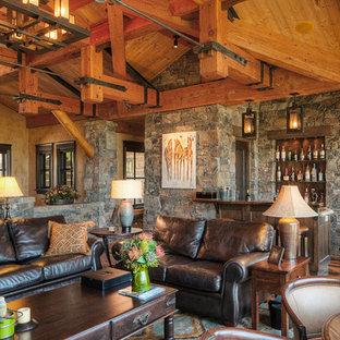 Esempio di un grande soggiorno rustico aperto con sala formale, pareti grigie, parquet scuro, camino classico, cornice del camino in pietra, nessuna TV e pavimento marrone