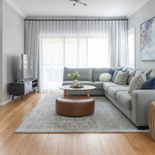 シドニーの広いコンテンポラリースタイルのおしゃれな独立型リビング (グレーの壁、無垢フローリング、茶色い床、標準型暖炉、石材の暖炉まわり、据え置き型テレビ、羽目板の壁) の写真