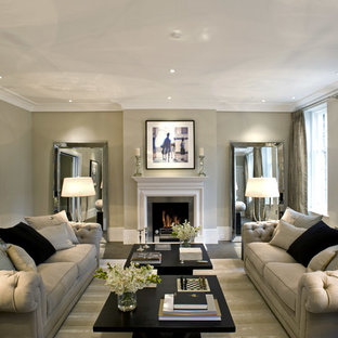 Inspiration for a transitional enclosed living room remodel in London with beige walls and a standard fireplace