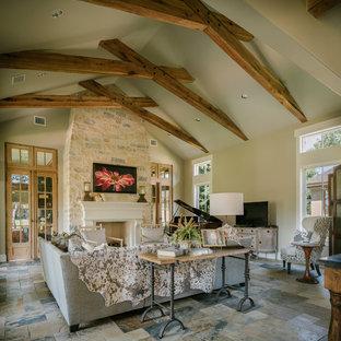 ヒューストンの広いラスティックスタイルのおしゃれなLDK (グレーの壁、スレートの床、標準型暖炉、石材の暖炉まわり、内蔵型テレビ) の写真
