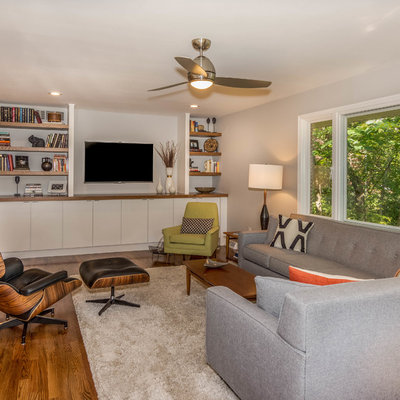 Mid-sized mid-century modern open concept medium tone wood floor and brown floor living room photo in Other with gray walls, a two-sided fireplace and a brick fireplace
