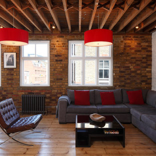 Design ideas for a large industrial open concept living room in London with white walls, light hardwood floors, no fireplace, no tv, brown floor, exposed beam and brick walls.