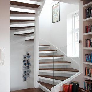 Réalisation d'un grand salon design ouvert avec un mur blanc, un sol en bois clair, aucune cheminée, aucun téléviseur, un sol marron, un plafond en poutres apparentes et un mur en parement de brique.