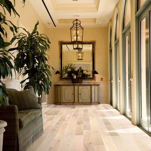 ロサンゼルスの中サイズのトロピカルスタイルのおしゃれなLDK (黄色い壁、淡色無垢フローリング、暖炉なし、テレビなし、ベージュの床) の写真
