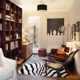 Inspiration for a small eclectic enclosed living room in London with a reading nook, white walls, medium hardwood flooring and brown floors.