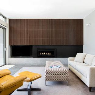 Imagen de salón abierto y madera, moderno, de tamaño medio, madera, con paredes grises, suelo de cemento, chimenea tradicional, marco de chimenea de metal, televisor retractable, suelo gris y madera