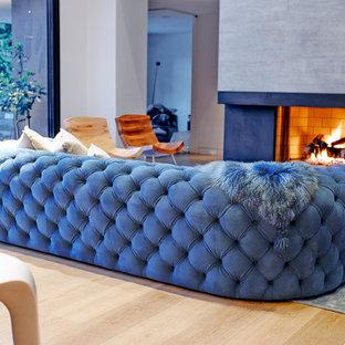 Foto di un soggiorno design di medie dimensioni e aperto con pareti bianche, parquet chiaro, camino classico, cornice del camino in cemento e parete attrezzata