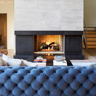 Ispirazione per un soggiorno design di medie dimensioni e aperto con pareti bianche, parquet chiaro, camino classico, cornice del camino in cemento e parete attrezzata