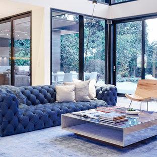 Immagine di un soggiorno design di medie dimensioni e stile loft con pareti bianche, pavimento in legno massello medio, camino classico, cornice del camino in cemento e nessuna TV