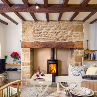 Living room - small cottage enclosed carpeted living room idea in Gloucestershire with white walls, a wood stove, a tv stand and a stone fireplace