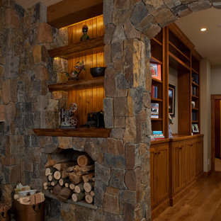 Example of a huge classic open concept medium tone wood floor living room design in Grand Rapids with white walls, a standard fireplace, a stone fireplace and a wall-mounted tv