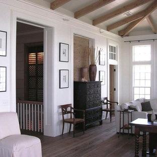 マイアミの中サイズのトロピカルスタイルのおしゃれな独立型リビング (フォーマル、白い壁、濃色無垢フローリング、標準型暖炉、タイルの暖炉まわり) の写真