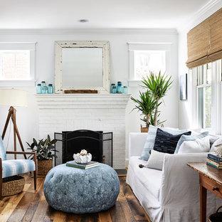 ワシントンD.C.のビーチスタイルのおしゃれなリビング (白い壁、無垢フローリング、標準型暖炉、レンガの暖炉まわり、茶色い床) の写真