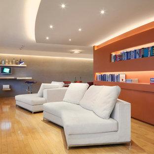 Modelo de biblioteca en casa abierta, contemporánea, pequeña, sin chimenea, con parades naranjas, suelo de madera clara y televisor colgado en la pared