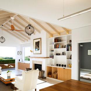 Idées déco pour un petit salon bord de mer ouvert avec un mur blanc, un sol en bois peint, une cheminée standard, un manteau de cheminée en pierre, un téléviseur encastré, un sol blanc, un plafond en poutres apparentes et du lambris de bois.