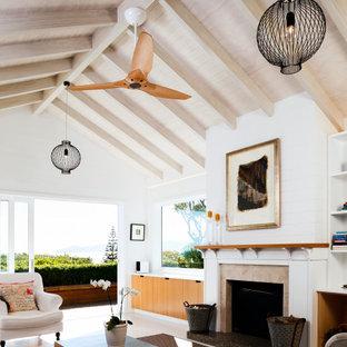 ウェリントンの小さいビーチスタイルのおしゃれなLDK (白い壁、塗装フローリング、標準型暖炉、石材の暖炉まわり、埋込式メディアウォール、白い床、表し梁、塗装板張りの壁) の写真