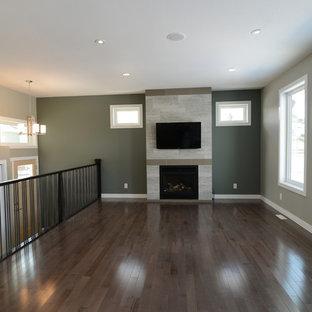 Immagine di un soggiorno stile americano di medie dimensioni e stile loft con pareti verdi, pavimento in vinile, camino classico, cornice del camino in pietra e TV a parete
