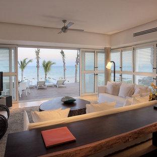 マイアミの中くらいのトロピカルスタイルのおしゃれなリビング (白い壁、ライムストーンの床、暖炉なし、据え置き型テレビ) の写真
